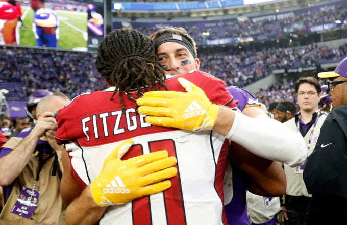 Minnesota Vikings wide receiver Adam Thielen gets a hug from Arizona Cardinals wide receiver Larry Fitzgerald, left, after an NFL football game, Sunday, Oct. 14, 2018, in Minneapolis. The Vikings won 27-17. (AP Photo/Bruce Kluckhohn)