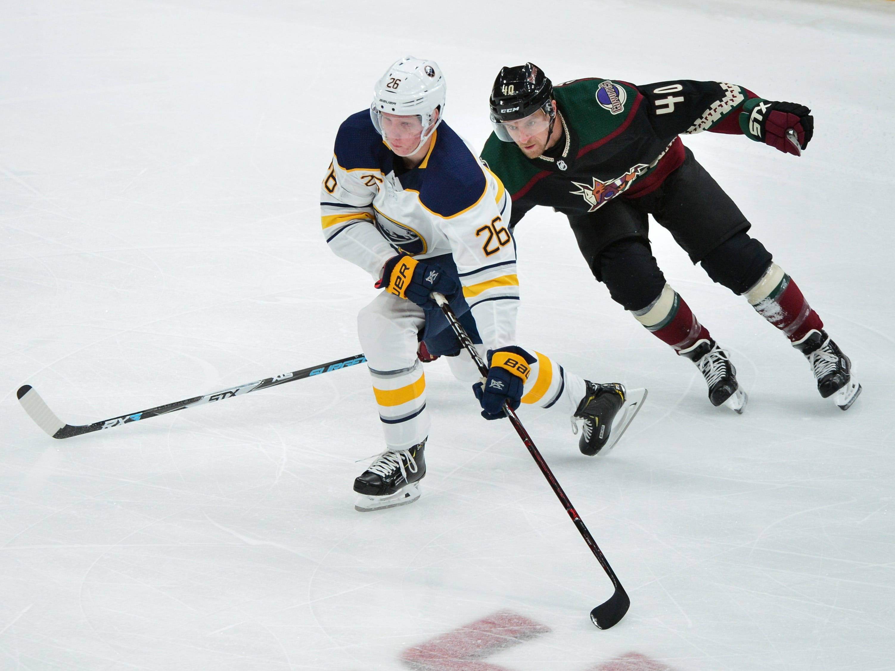 Oct 13, 2018; Glendale, AZ, USA; Buffalo Sabres defenseman Rasmus Dahlin (26) carries the puck past Arizona Coyotes right wing Michael Grabner (40) during the first period at Gila River Arena.