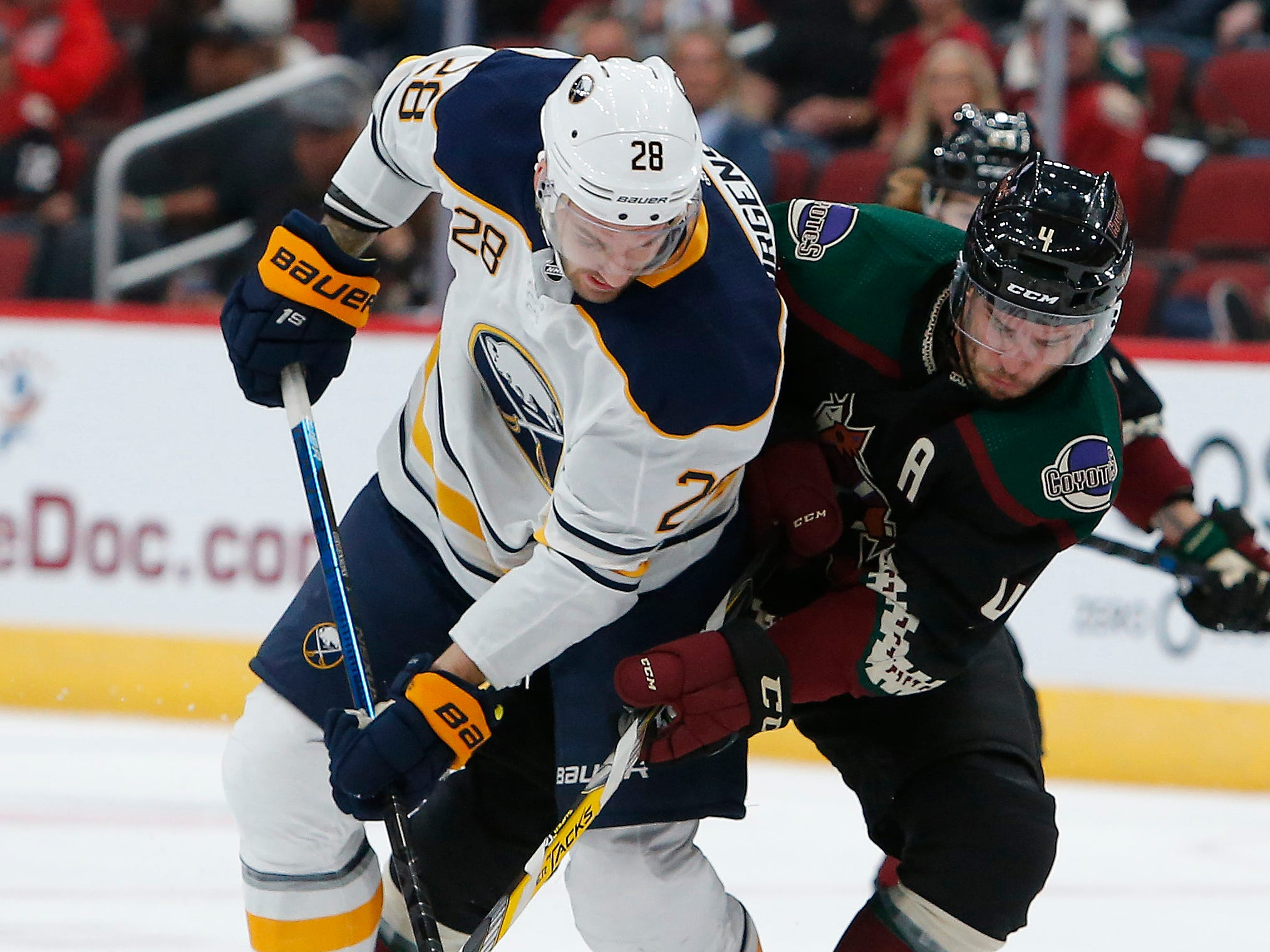 Buffalo Sabres center Zemgus Girgensons (28) and Arizona Coyotes defenseman Niklas Hjalmarsson battle for the puck and in the first period during an NHL hockey game, Saturday, Oct. 13, 2018, in Glendale, Ariz.