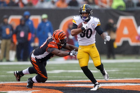 Pittsburgh Steelers running back James Conner (30) runs the ball past Cincinnati Bengals defensive tackle Geno Atkins, left, in the second half of an NFL football game, Sunday, Oct. 14, 2018, in Cincinnati. (AP Photo/Gary Landers)
