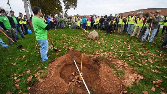 Volunteer PJ Piccone describes to a circle of more than 100 volunteers who showed up in Springfield Township to help plant the trees Sunday. The Rotary only expected 60 volunteers.