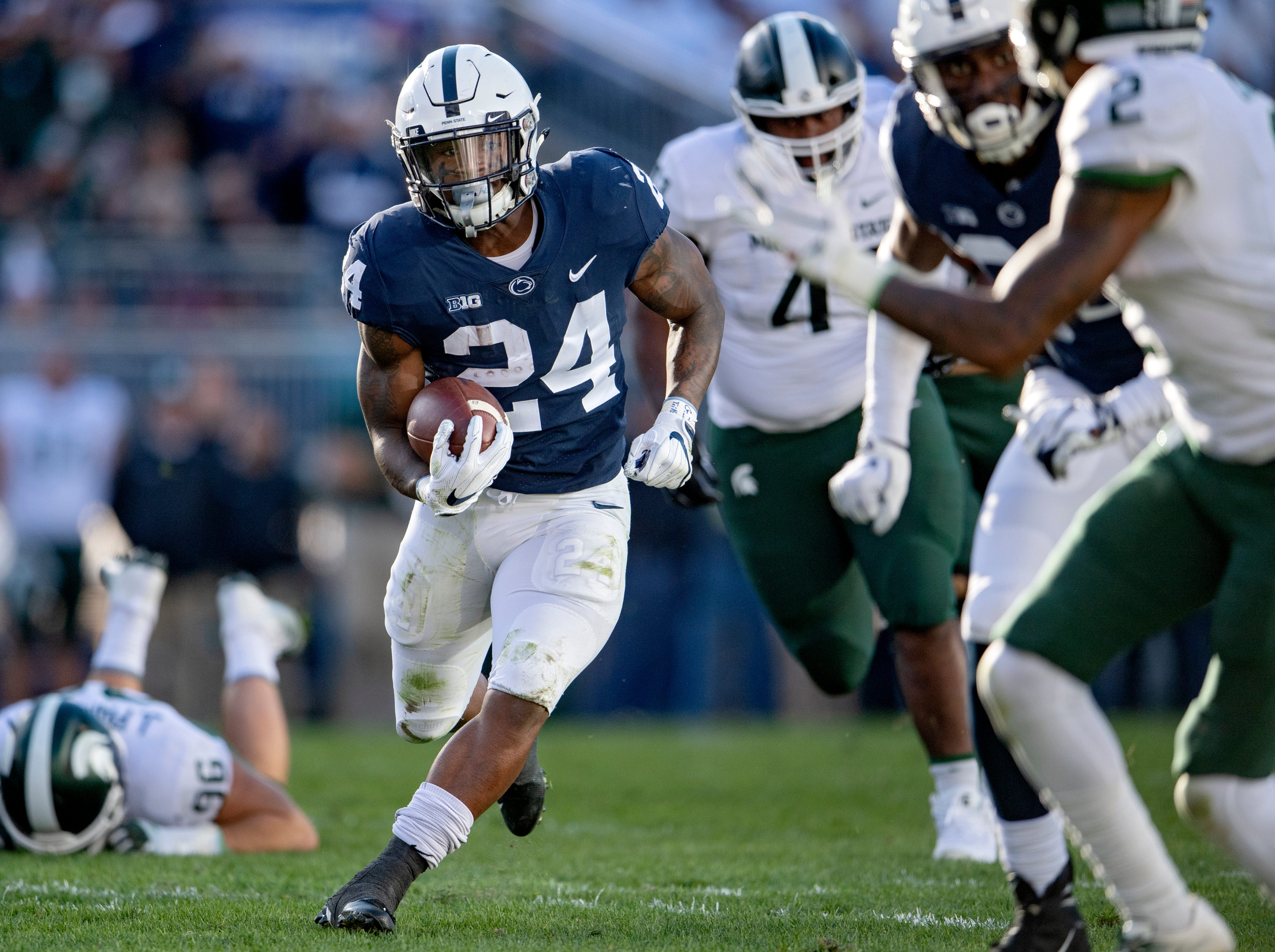 Penn State running back Miles Sanders runs downfield while dodging Michigan State defenders for a touchdown during an NCAA college football game Saturday, Oct. 13, 2018, in State College, Pa.