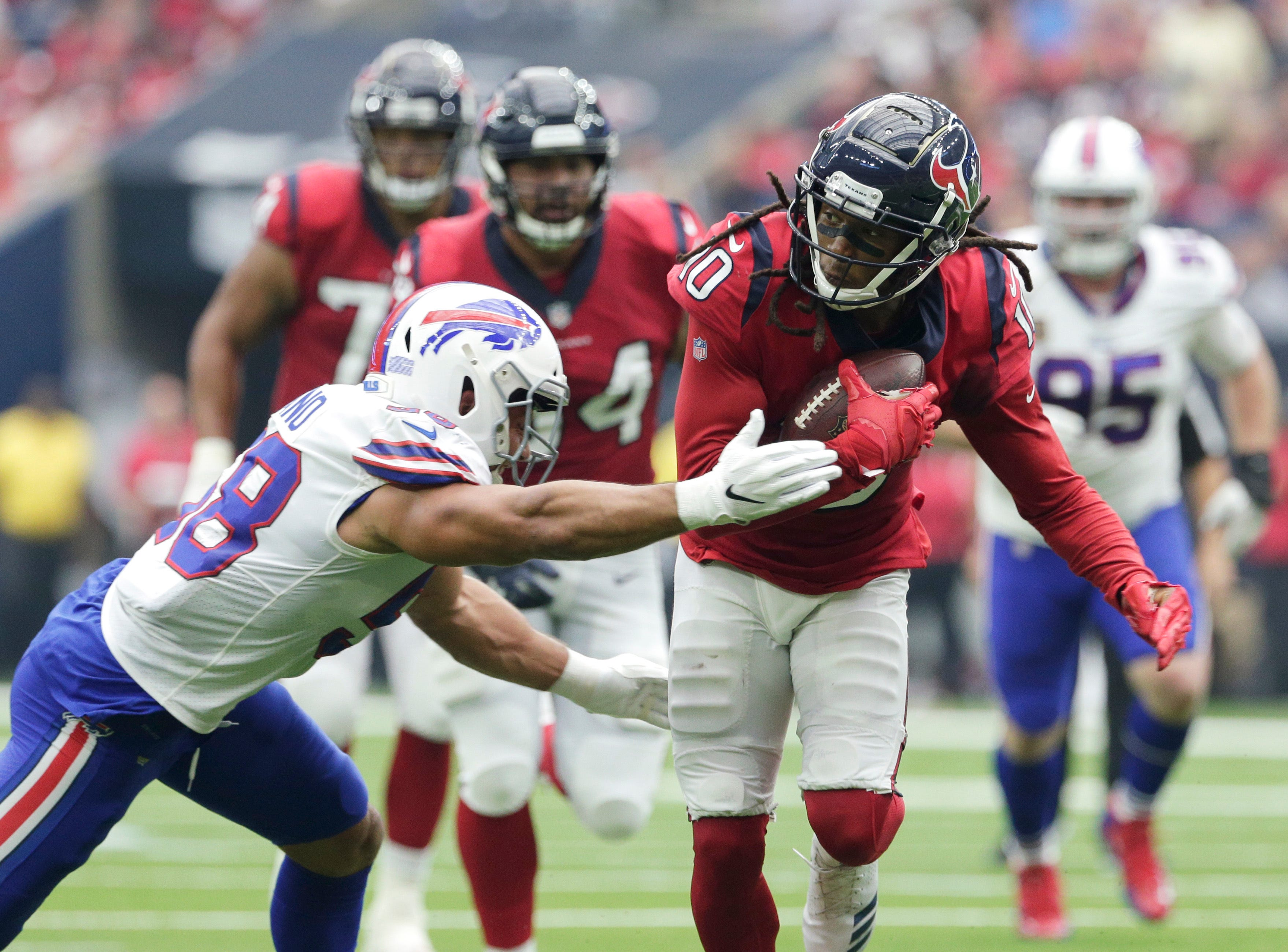 Houston Texans wide receiver DeAndre Hopkins (10) is hit by Buffalo Bills linebacker Matt Milano (58) during the first half of an NFL football game, Sunday, Oct. 14, 2018, in Houston. (AP Photo/Michael Wyke)