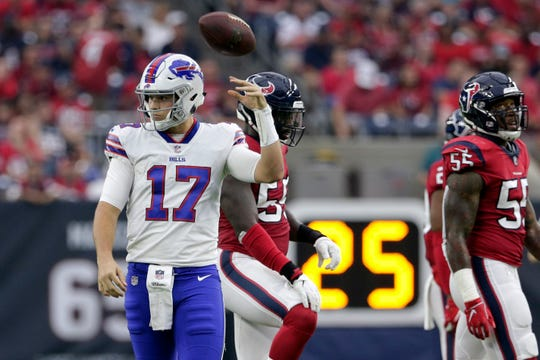 Buffalo Bills quarterback Josh Allen (17) tosses the ball back after he was sacked during the first half of an NFL football game against the Houston Texans.