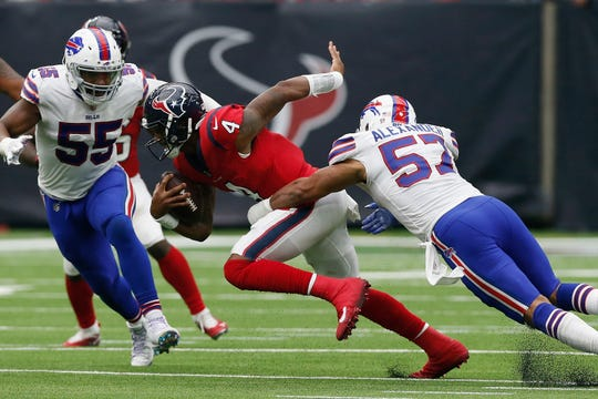 Deshaun Watson of the Houston Texans is sacked by Lorenzo Alexander(57)  of the Buffalo Bills as Jerry Hughes (55) closes in during the fourth quarter of Sunday's game at Houston.