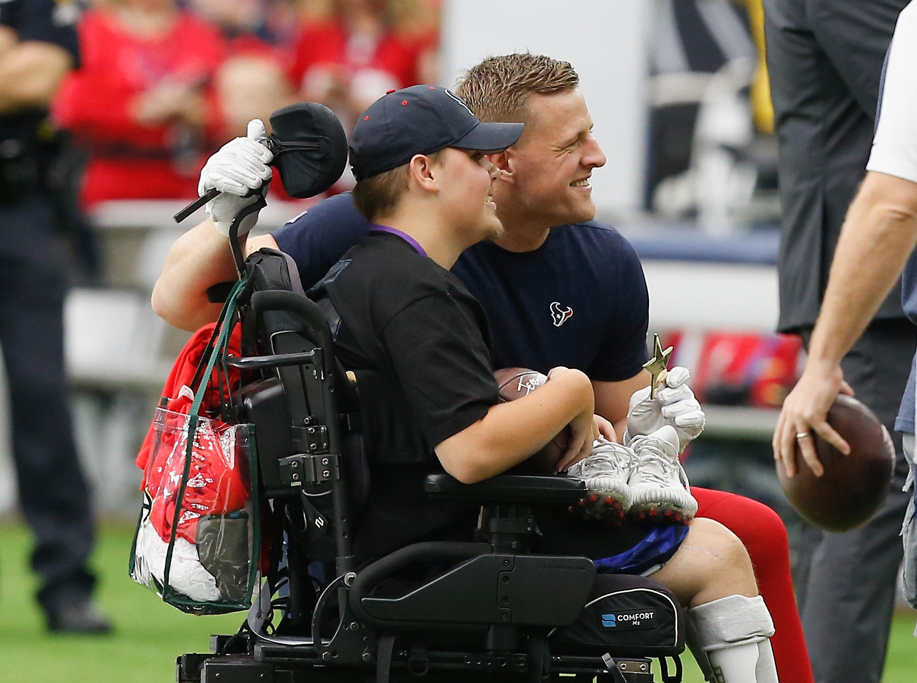 HOUSTON, TX - OCTOBER 14:  J.J. Watt #99 of the Houston Texans poses witht a  fan during pre-game warmups before playing the Buffalo Bills at NRG Stadium on October 14, 2018 in Houston, Texas.  (Photo by Bob Levey/Getty Images)