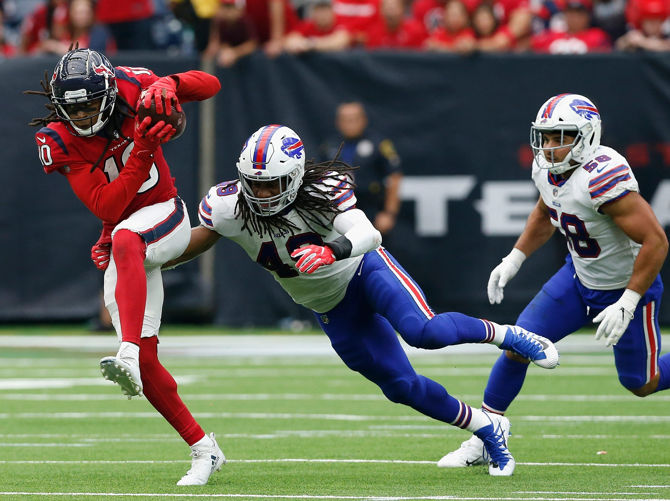 HOUSTON, TX - OCTOBER 14:  DeAndre Hopkins #10 of the Houston Texans runs after a catch in the fourth quarter defended by Tremaine Edmunds #49 of the Buffalo Bills at NRG Stadium on October 14, 2018 in Houston, Texas.  (Photo by Tim Warner/Getty Images)