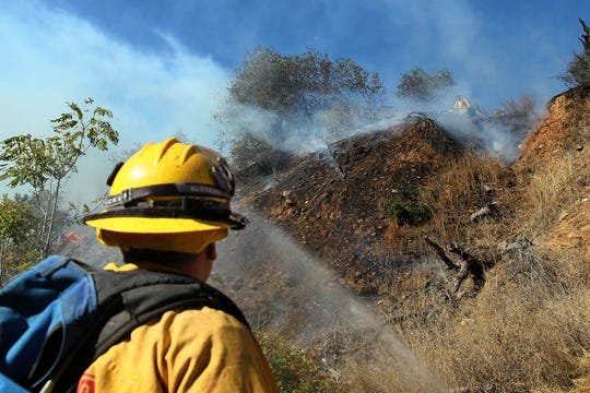 Firefighters in Redding fight the Masonic Fire on Oct. 14, 2018. Entrepreneurs are trying to develop spray-on products to keep vegetation from catching fire.