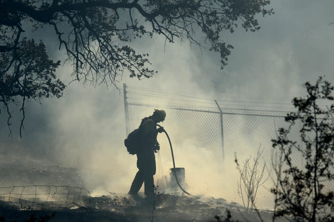 A firefighter puts out a hot spot with a water hose in the area along Sulphur Creek Road on Sunday morning, Oct. 14, 2018. (Hung T. Vu/Special to the Record Searchlight)
