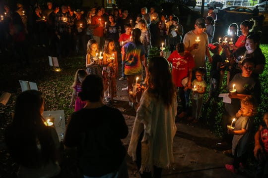 Residents gather in front of the courthouse of a candlelight vigil for all those affected by the flood Saturday, Oct. 13, 2018, in Junction.