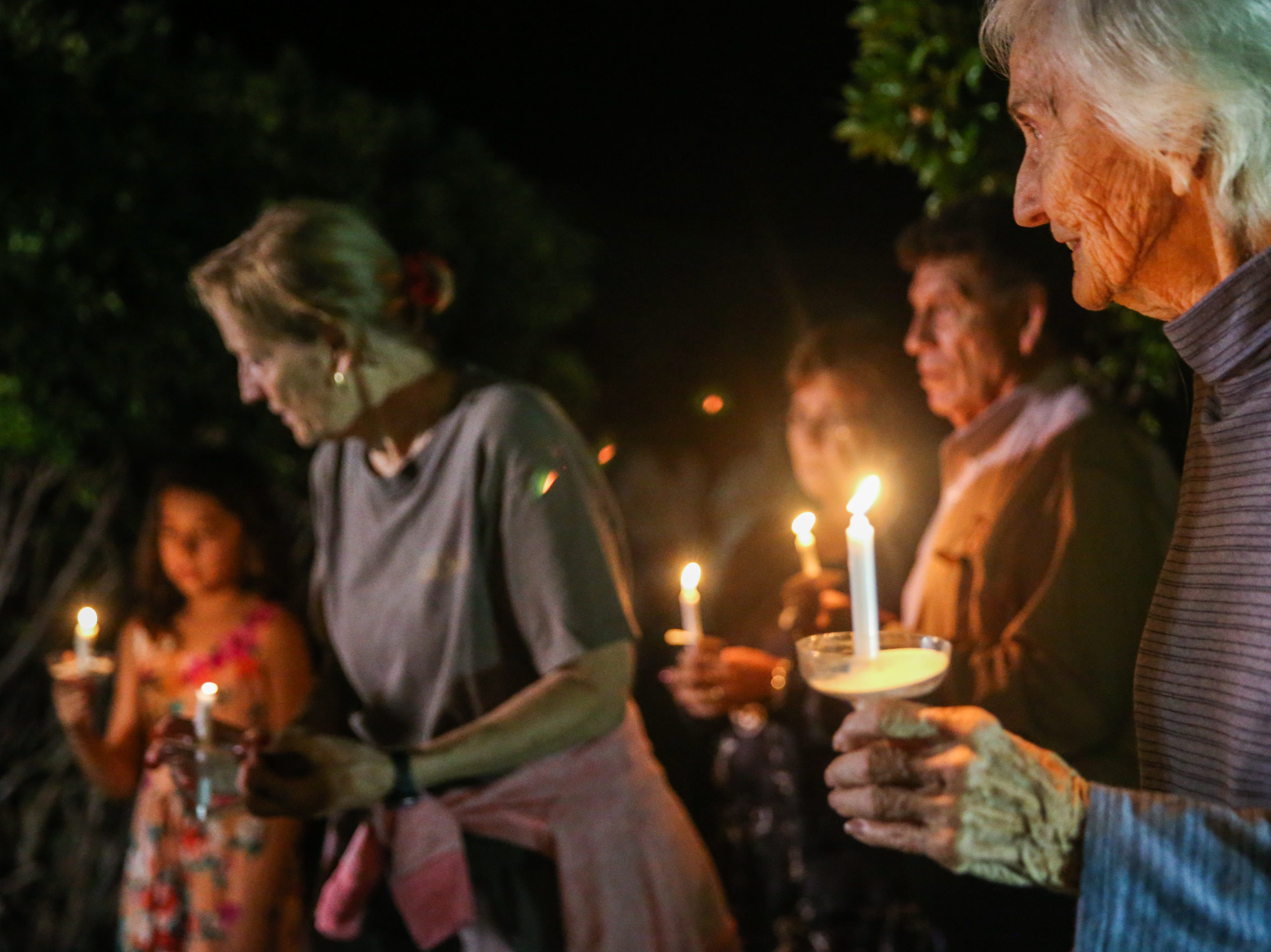 Residents hold up candles during a vigil for all those affected by the flood Saturday, Oct. 13, 2018, in Junction.