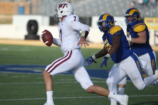 West Texas A&M quarterback Justin Houghtaling tries to elude the Angelo State defense during a Lone Star Conference football game at LeGrand Stadium at 1st Community Credit Union Field on Saturday, Oct. 13, 2018. West Texas on 26-18 to spoil ASU's homecoming.