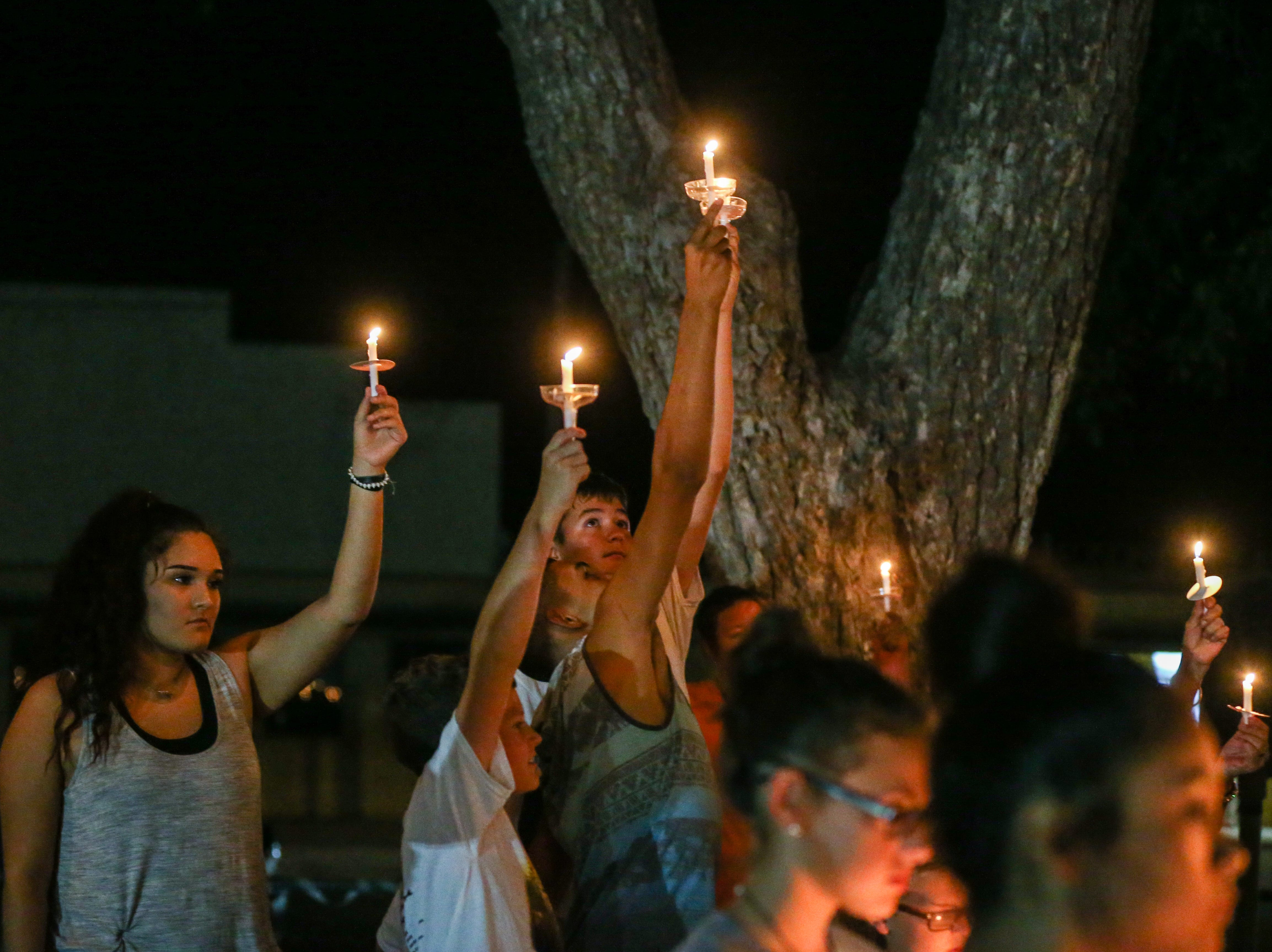 Residents hold up candles while singing 'Amazing Grace' during a vigil for all those affected by the flood Saturday, Oct. 13, 2018, in Junction.
