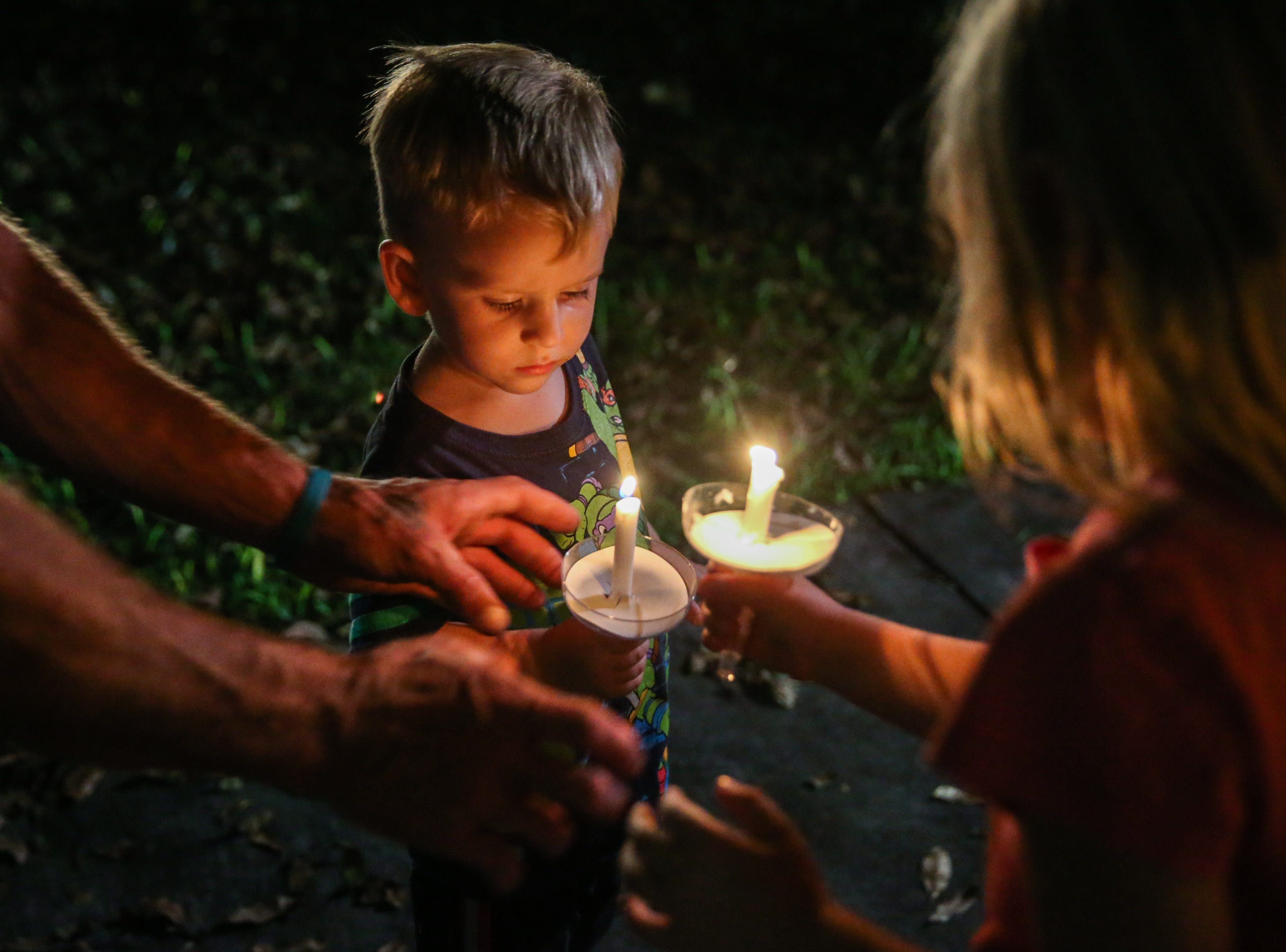 Lucas West, 2, takes a candle to hold during a vigil for all those affected by the flood Saturday, Oct. 13, 2018, in Junction.