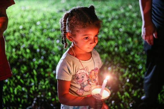 Chloe Smith, 3, holds a candle during a vigil for all those affected by the flood Saturday, Oct. 13, 2018, in Junction.