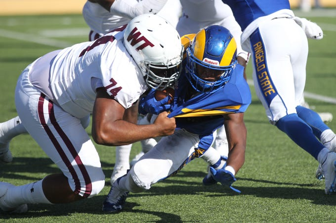 Angelo State University running back Tyrese Nathan almost gets his jersey ripped when tackled by West Texas A&M's Xavier Rivera during a Lone Star Conference football game at LeGrand Stadium at 1st Community Credit Union Field on Saturday, Oct. 13, 2018.
