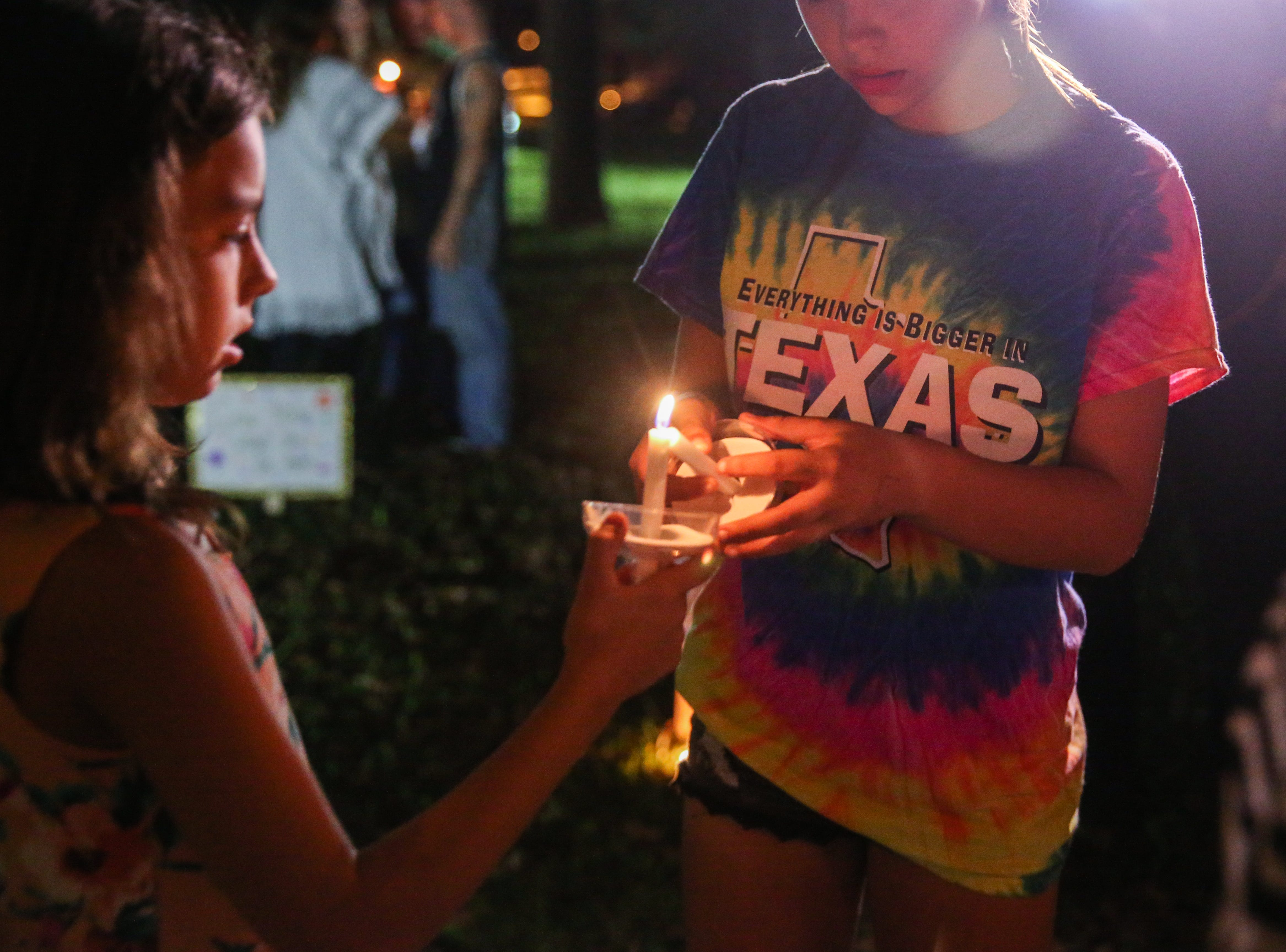 Kids light their candles for a vigil for all those affected by the flood Saturday, Oct. 13, 2018, in Junction.