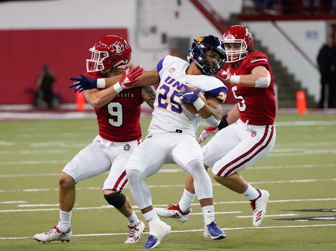University of South Dakota defenders Andrew Gray (9) and Brian Woodward attempt to tackle UNI running back Trevor Allen on Saturday in Vermillion.