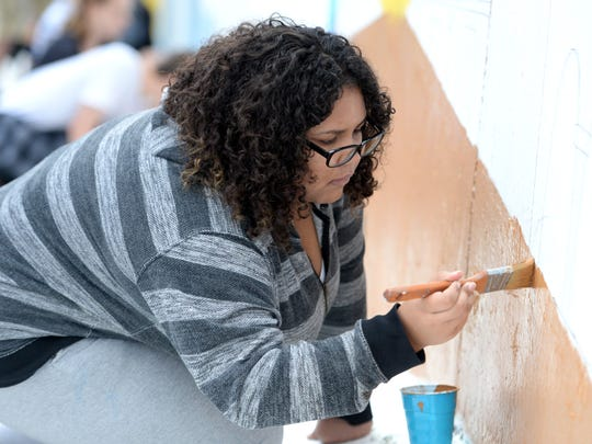 Fort Defiance sophomore Christal Fomby helps paint the school's spirit wall Saturday, Oct. 13.