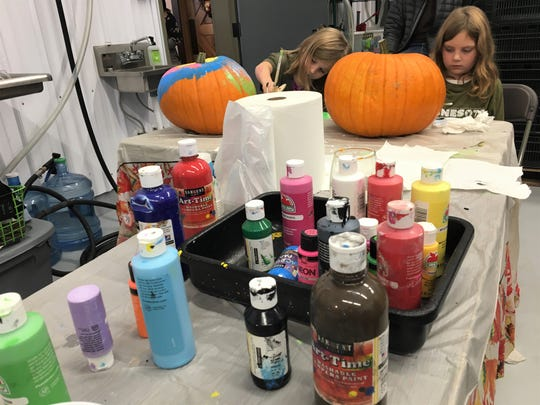 From left, Lydia Beirne, 4, and Claire Beirne, 7, each approach their pumpkin painting with their own style.