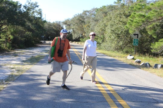 Jennifer LaVia and Jay LaVia walk on Alligator Point. The main roadway is completely washed out forcing people to walk out onto the peninsula to assess damage.