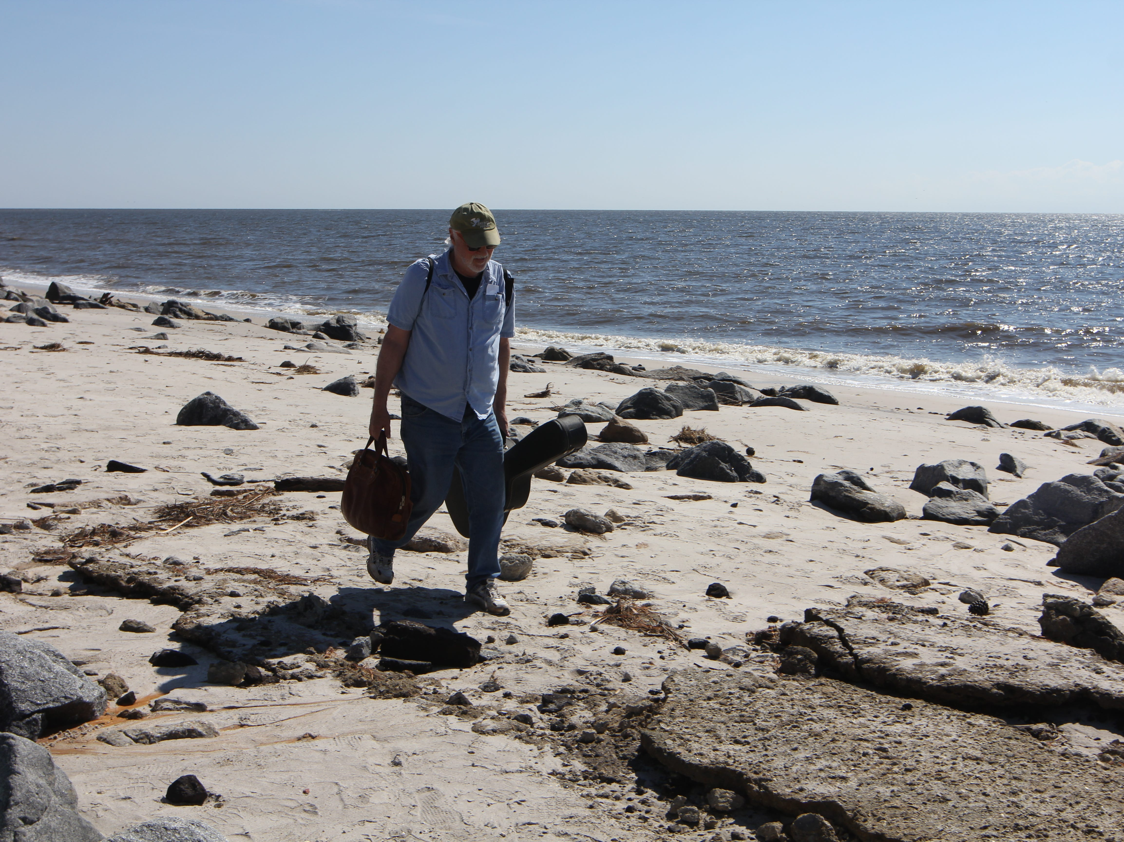Dean Newman, an Alligator Point resident, hikes in a guitar after the main road was washed out by Hurricane Michael. Newman took 10 guitars off the peninsula before the storm.