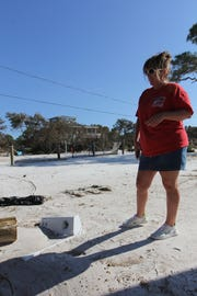 Tonia McNabb looks at her washer from her house on Alligator Point. It sustained major damage in Hurricane Michael.