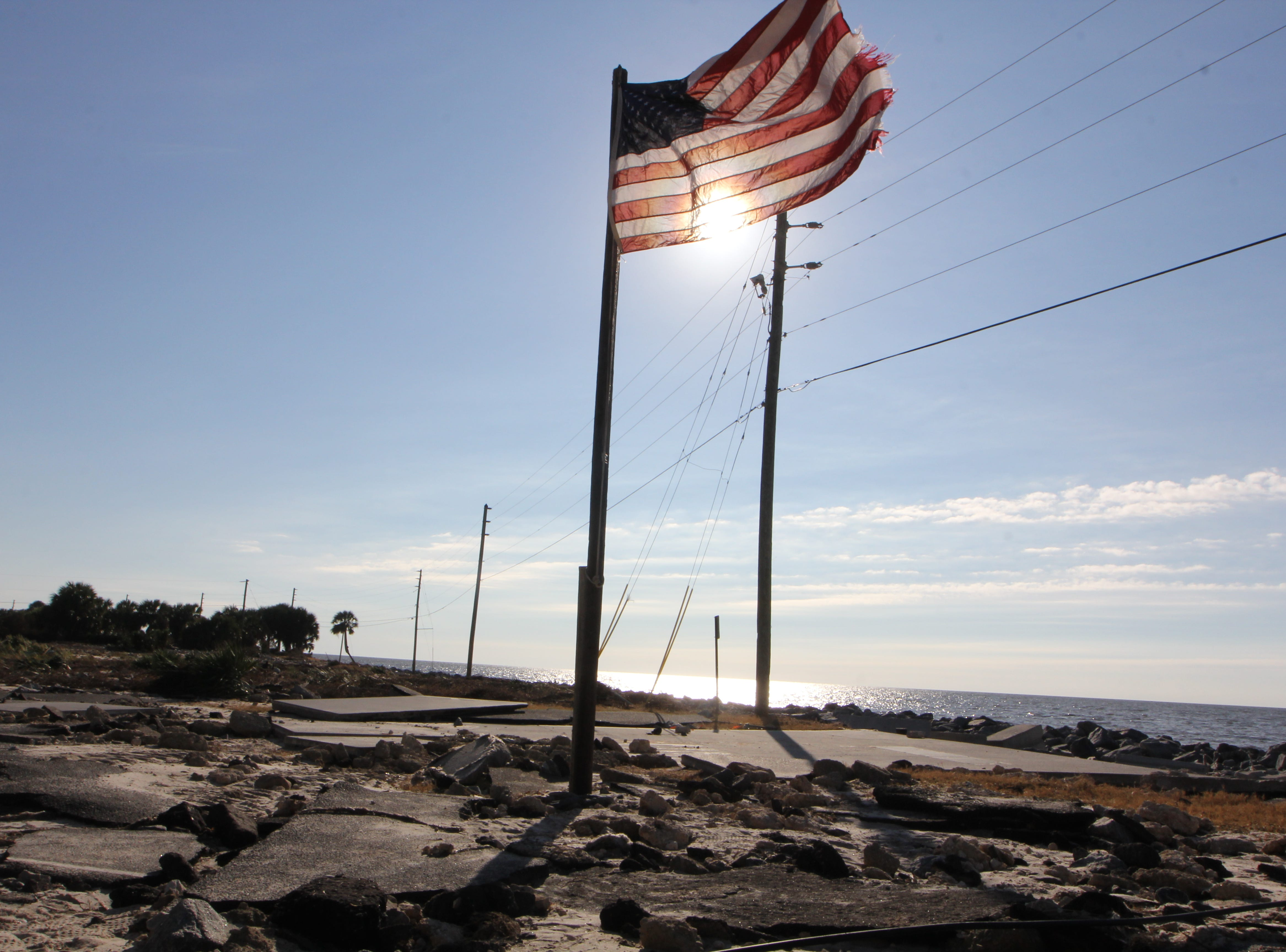 An American flag flaps in the wind amid rubble on Alligator Point.