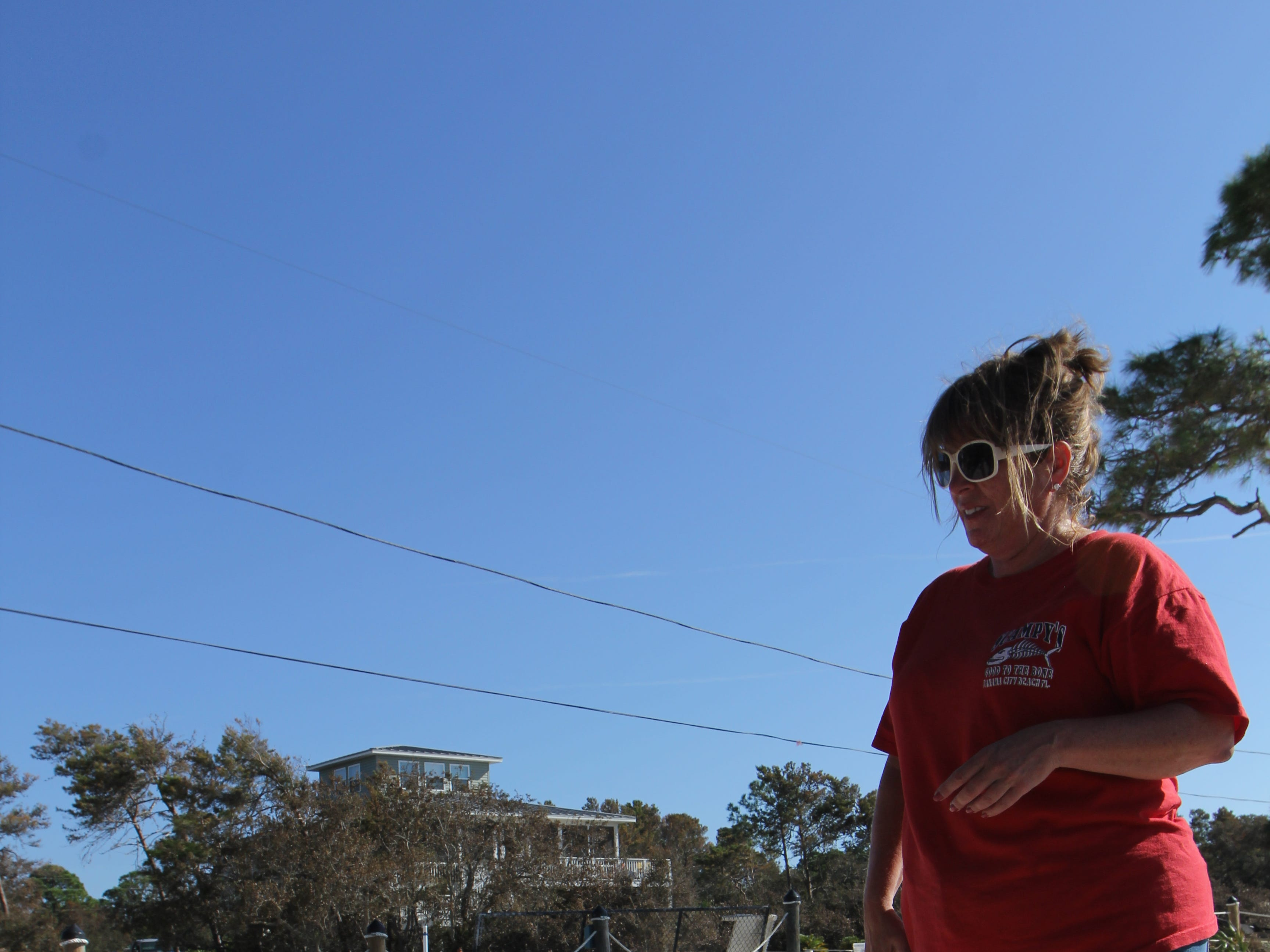 Tonia McNabb looks at the washer from her house on Alligator Point. It lies submerged beneath sand
