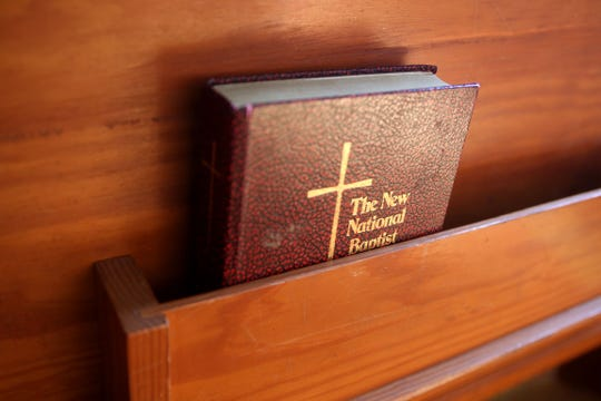 A hymnal rests in a church pew.