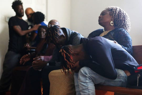 Jeanella Hall, 38, aunt, middle consoles Tyrone Grant, 23, left, and Tyran Grant, 21, right, sons of Demashell Bass, a woman who could not receive medical attention and died during the hurricane, at the Dream, Vision, and Destiny (DVD) Ministry in Gretna, Fla., on Sunday Oct. 14, 2018, after Hurricane Michael hits the Florida panhandle.