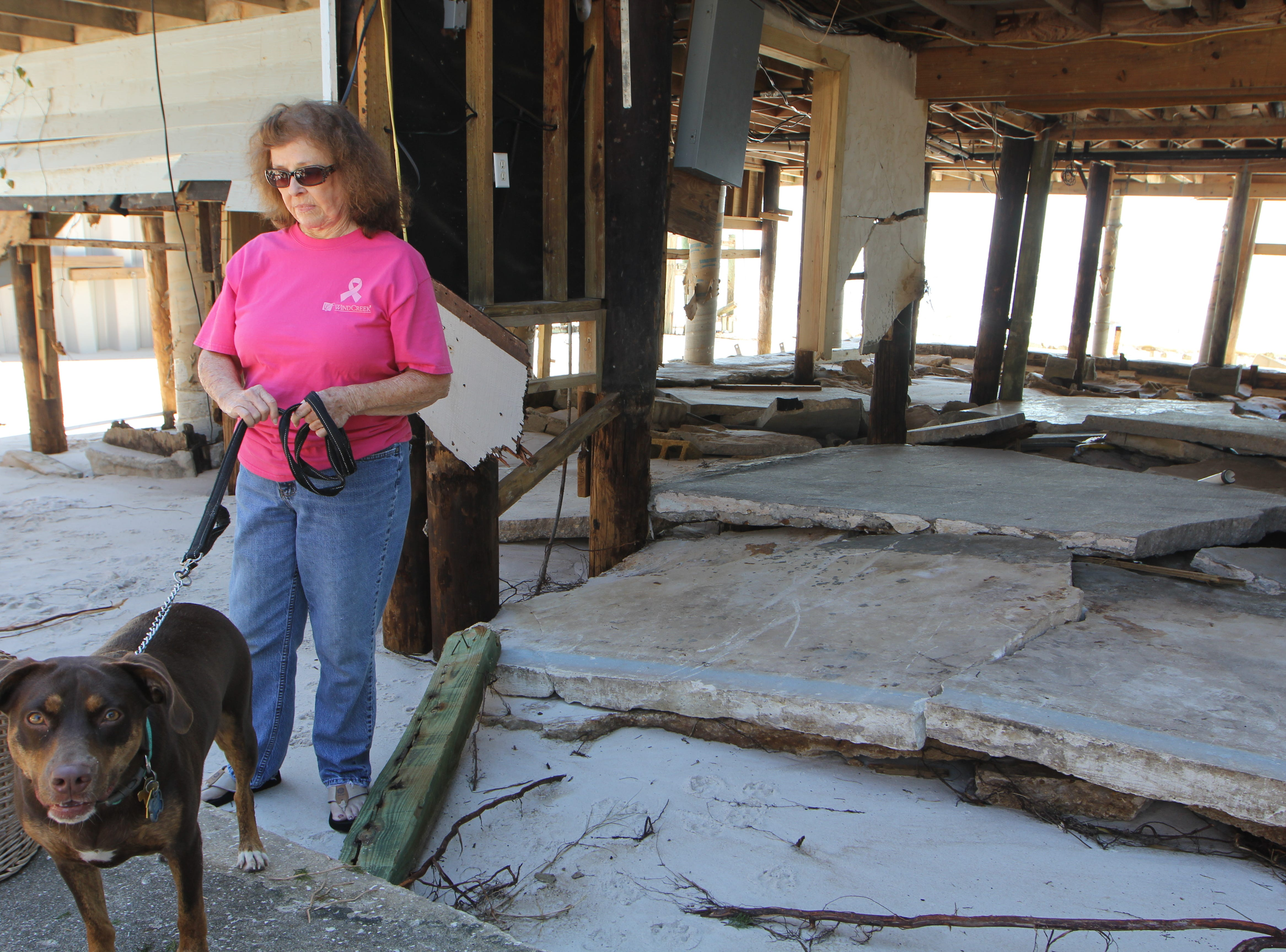 Jeanette Salas and dog Lucy stand in front of their family's Alligator Point home. It was damaged by Hurricane Michael.