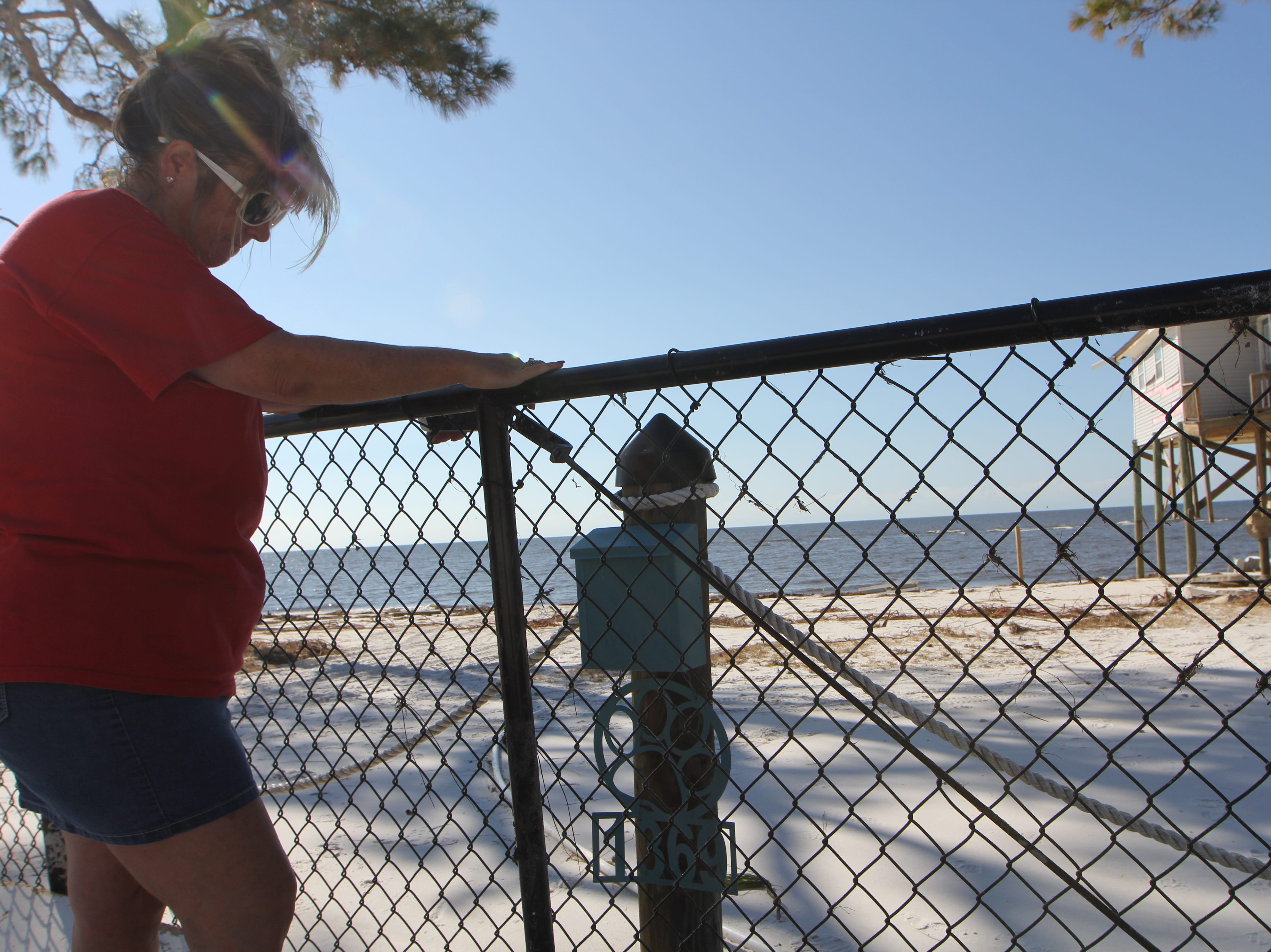 Tonia McNabb leans on the fence at her damaged house on Alligator Point.