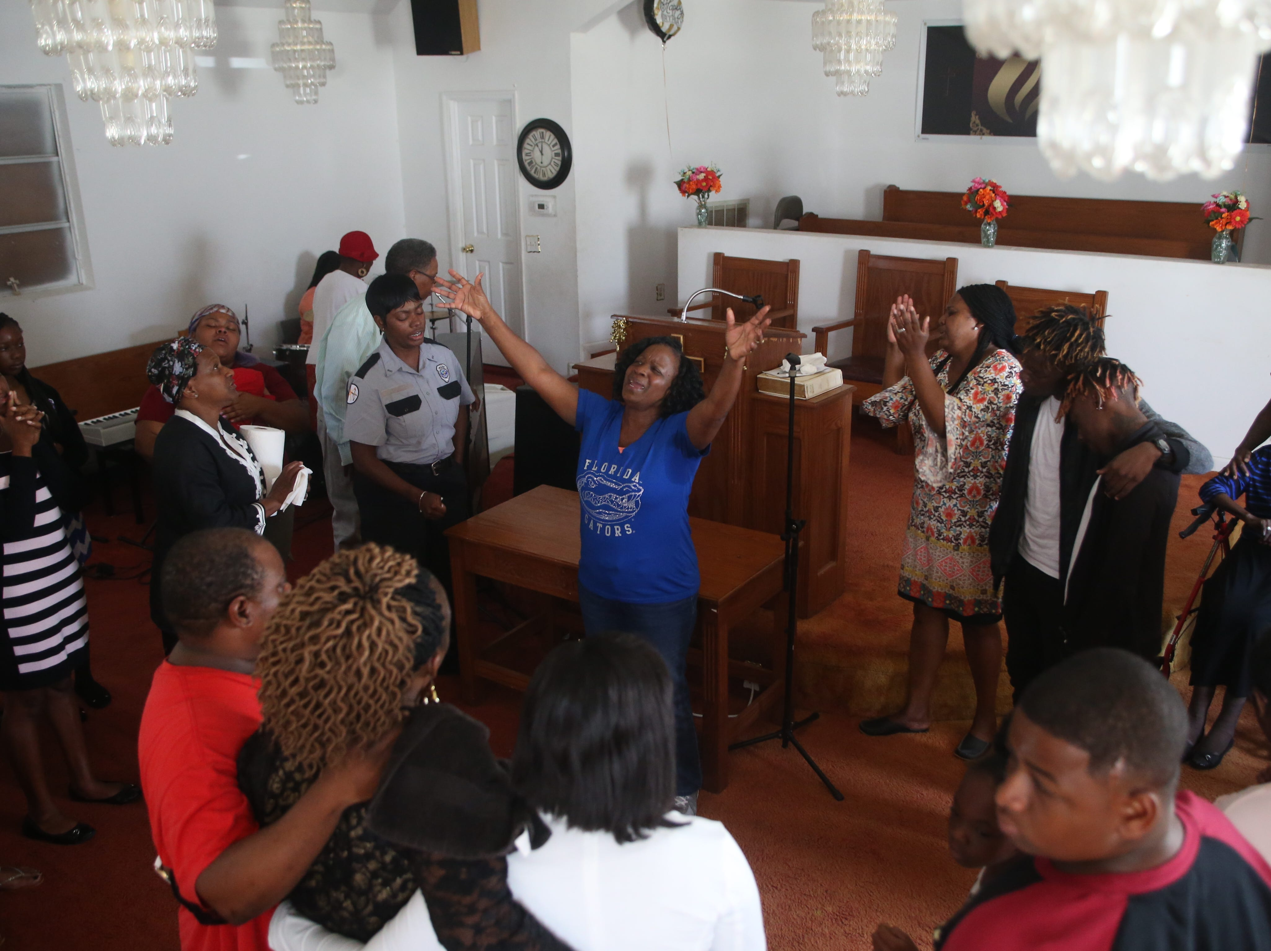 Church members surround Tyrone Grant and Tyran Grant sons of Demashell Bass, a woman who could not receive medical attention and died during the hurricane as they sing songs of worship at the Dream, Vision, and Destiny (DVD) Ministry in Gretna, Fla., on Sunday Oct. 14, 2018, after Hurricane Michael hits the Florida panhandle.