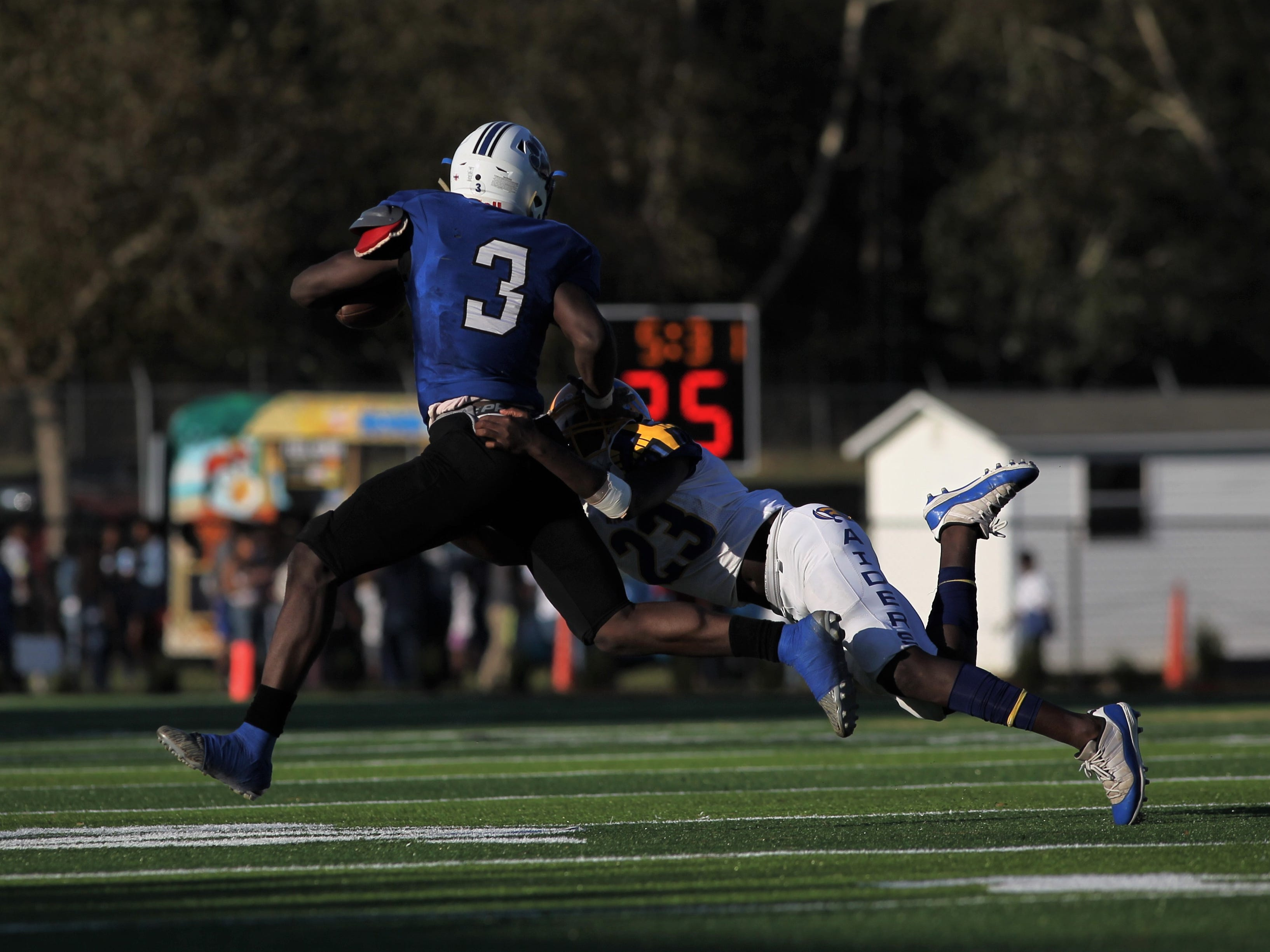 Godby running back Jaquez Yant tries to break the tackle of Rickards' Malik Franklin during Saturday's game.