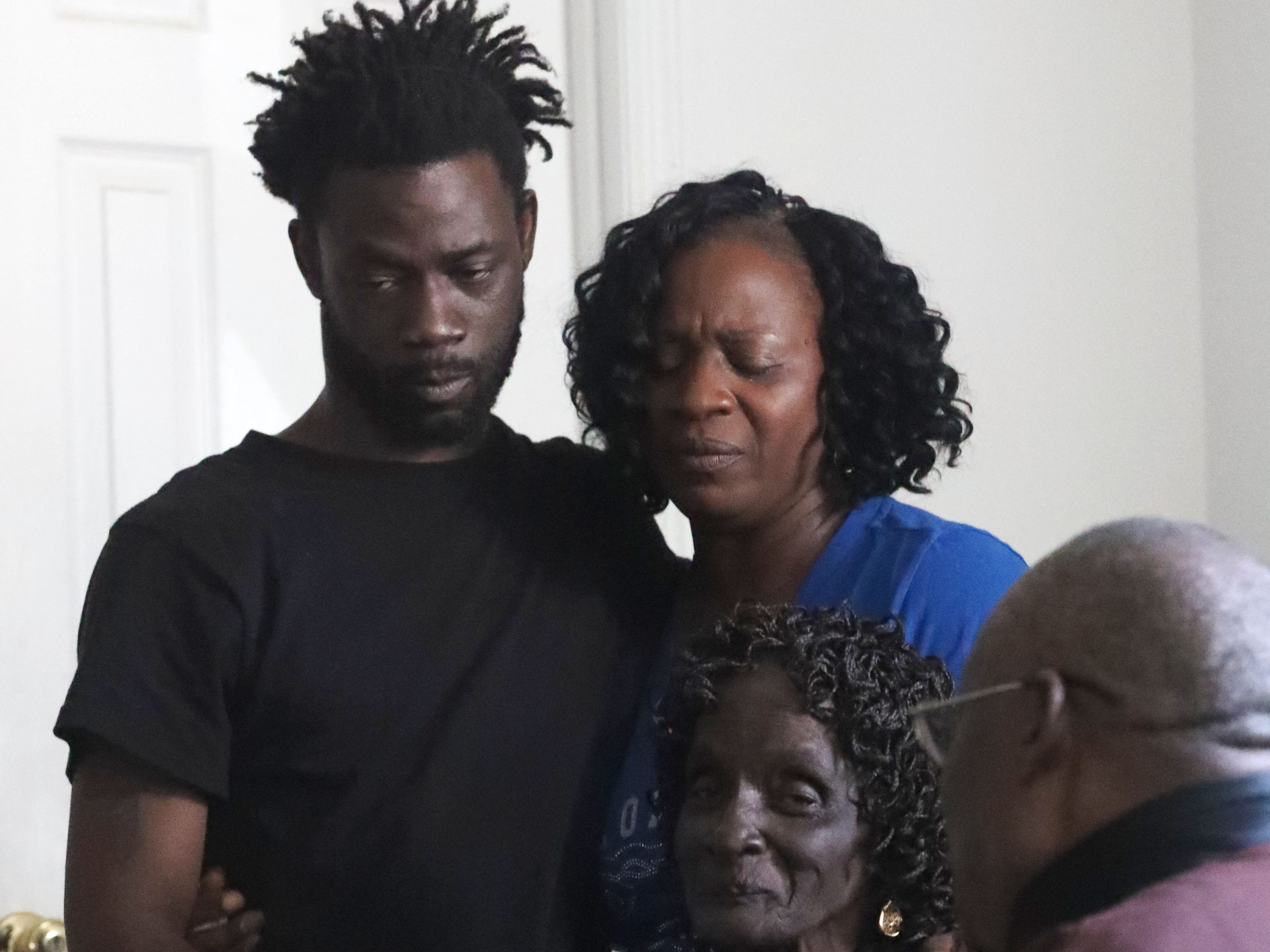 Lawrence Williams, 33, brother, left, Isabella Dubose, 54, aunt, middle, and Dollie Alls, 81, grandmother, right,  of Demashell Bass, a woman who could not receive medical attention and died during the hurricane fights back tears at the Dream, Vision, and Destiny (DVD) Ministry in Gretna, Fla., on Sunday Oct. 14, 2018, after Hurricane Michael hits the Florida panhandle.