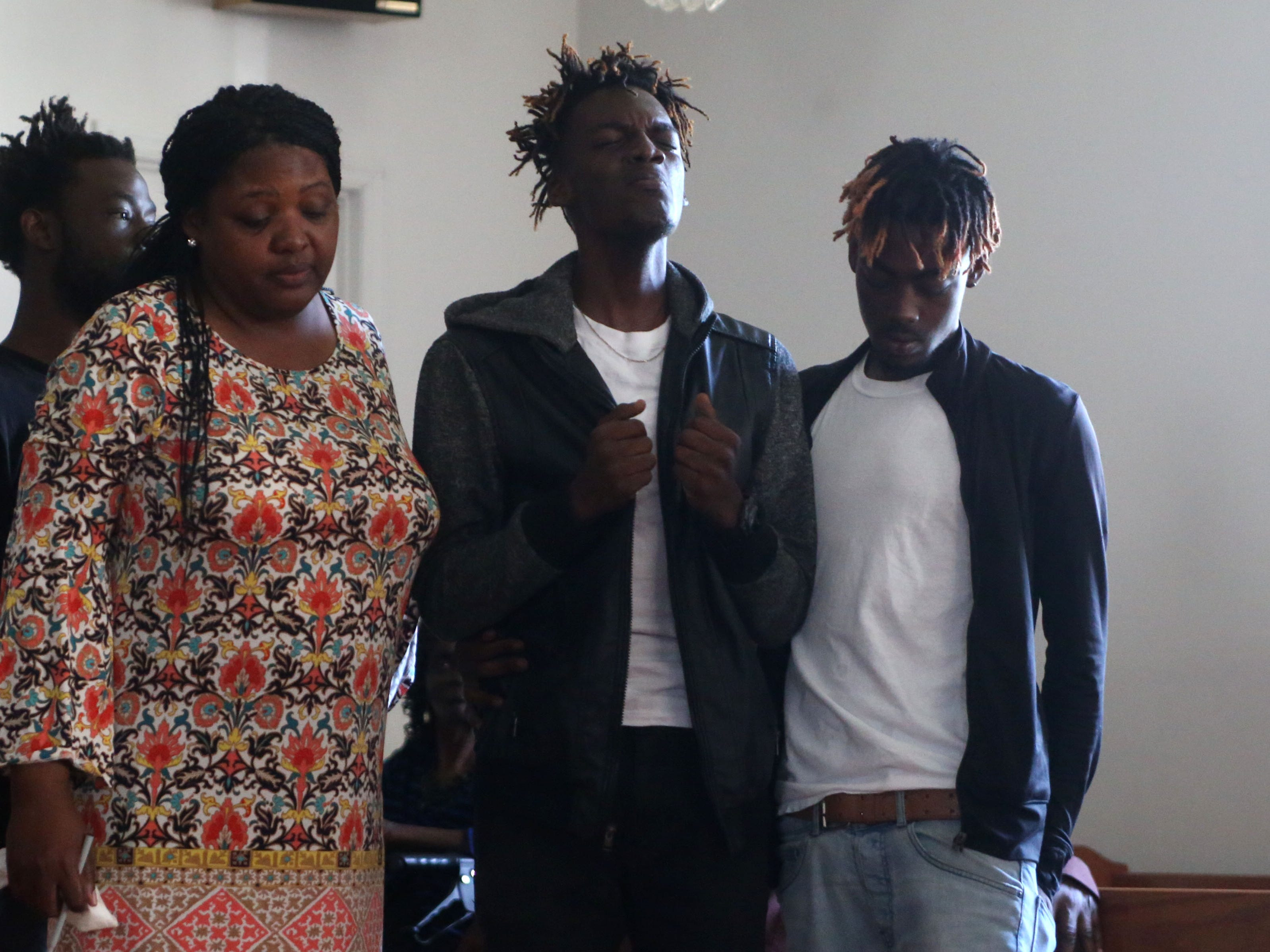 Delisha Green, left, friend, Tyrone Grant, middle and Tyran Grant, right, sons of Demashell Bass, a woman who could not receive medical attention and died during the hurricane, sing a hymn whilst trying to hold back tears at the Dream, Vision, and Destiny (DVD) Ministry in Gretna, Fla., on Sunday Oct. 14, 2018, after Hurricane Michael hits the Florida panhandle.
