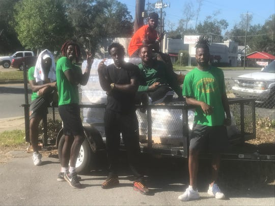Members of the FAMU football team pass out free water to those in need in Havana on Sunday, Oct. 14.
