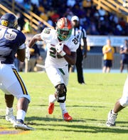 FAMU running back Ricky Henrilus dashes through the N.C. A&T defense.