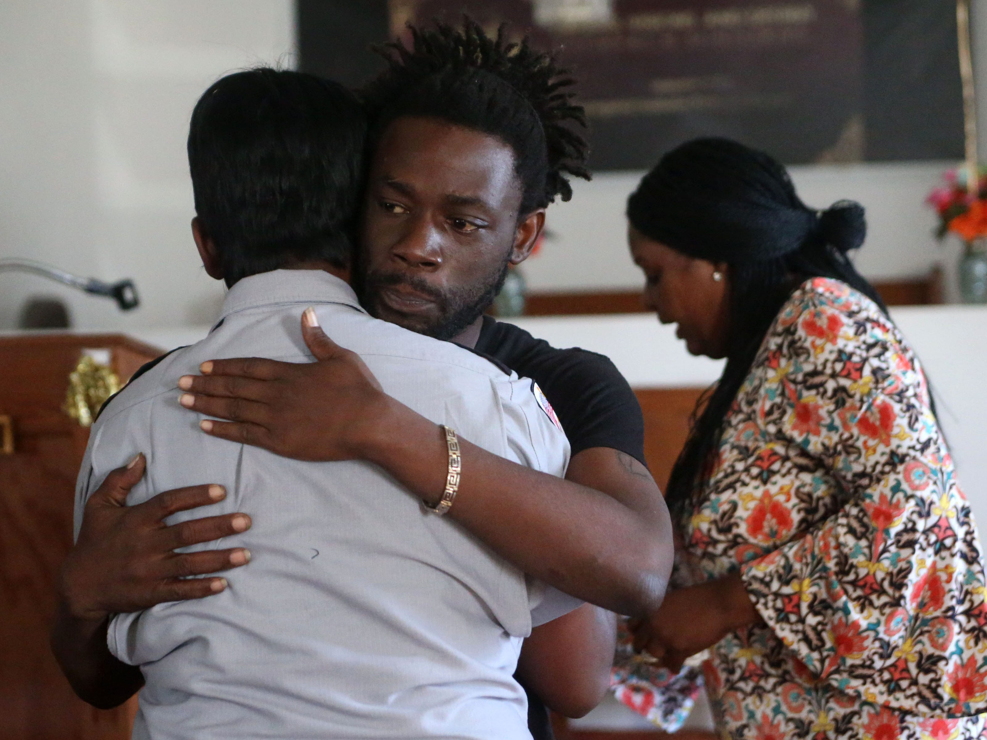 Lawrence Williams, brother of Demashell Bass, a woman who could not receive medical attention and died during the hurricane, 33, receives a comforting hug at the Dream, Vision, and Destiny (DVD) Ministry in Gretna, Fla., on Sunday Oct. 14, 2018, after Hurricane Michael hits the Florida panhandle.