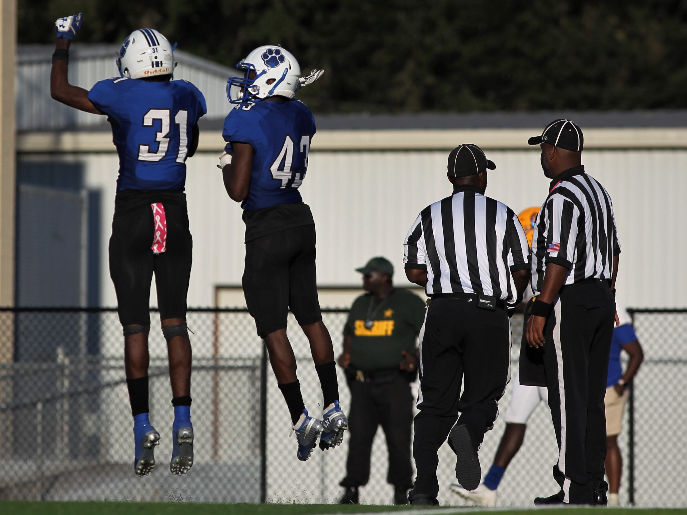 Godby's De'shawn Rucker (43) celebrates an interception with teammates during Saturday's game against Rickards.