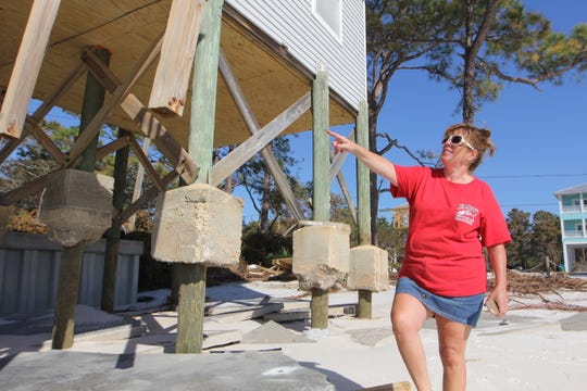Tonia McNabb stands near her wrecked house on Alligator Point. She lives in Atlanta but bought her home in May.