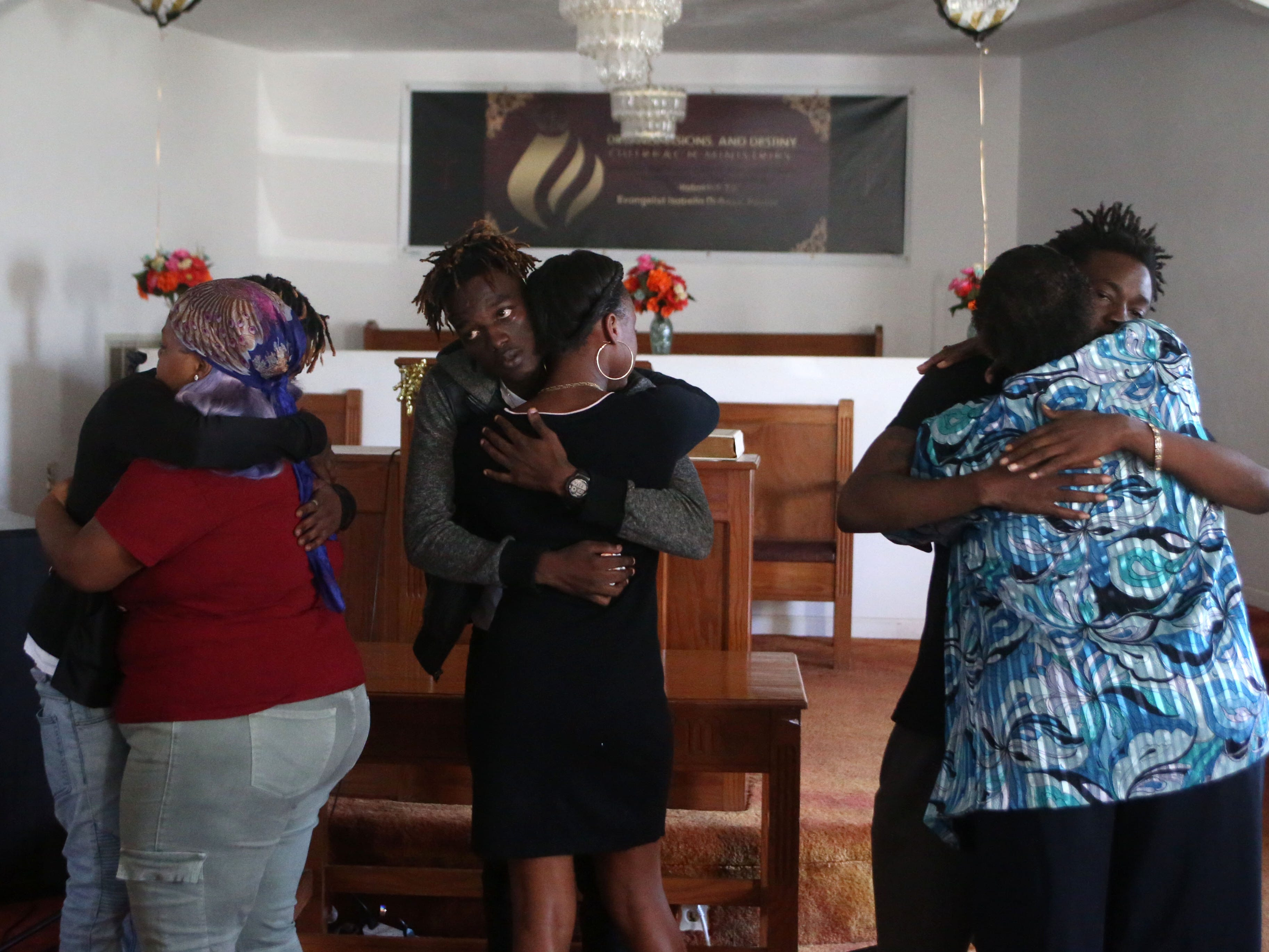 Family of Demashell Bass, a woman who could not receive medical attention and died during the hurricane from left to right, Tyran Grant, 21, son, Tyrone Grant, 23, son, and Lawrence Williams, 33, brother,  receive condolences from church members at the Dream, Vision, and Destiny (DVD) Ministry in Gretna, Fla., on Sunday Oct. 14, 2018, after Hurricane Michael hits the Florida panhandle.