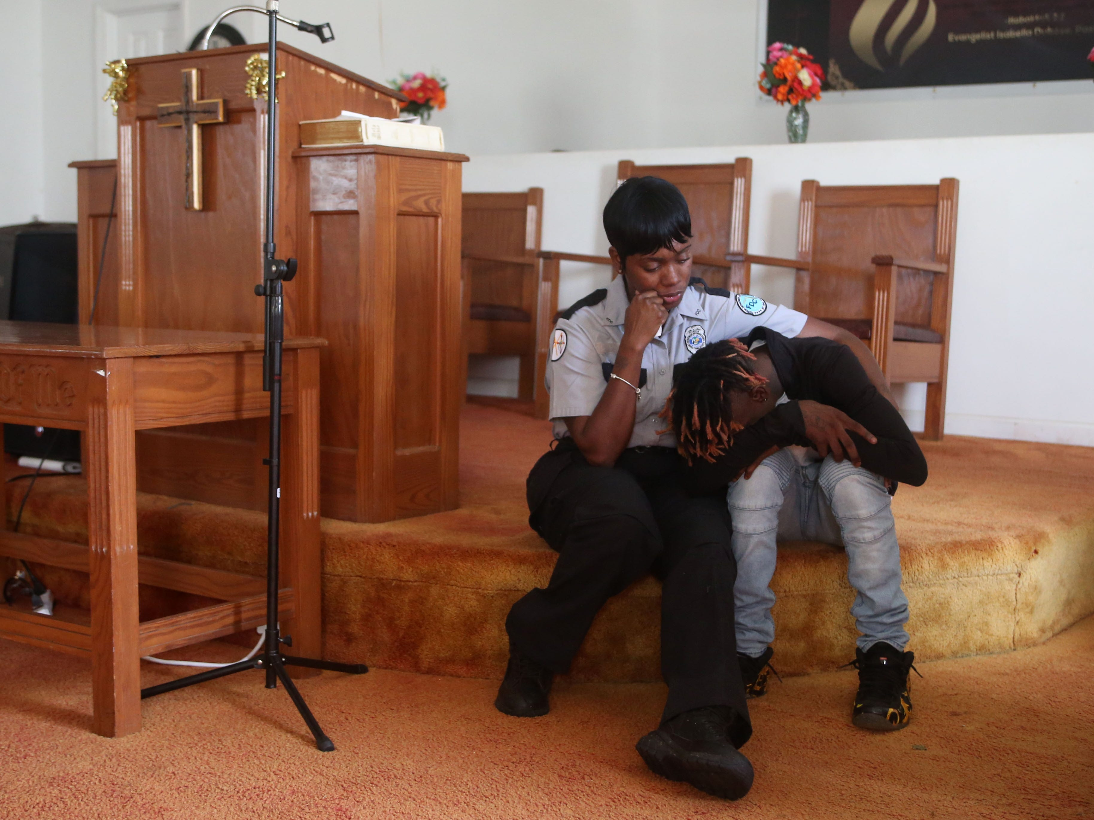 A church member tries to console Tyran Grant, 21, son of Demashell Bass, a woman who could not receive medical attention and died during the hurricane at the footsteps of the alter at the Dream, Vision, and Destiny (DVD) Ministry in Gretna, Fla., on Sunday Oct. 14, 2018, after Hurricane Michael hits the Florida panhandle.