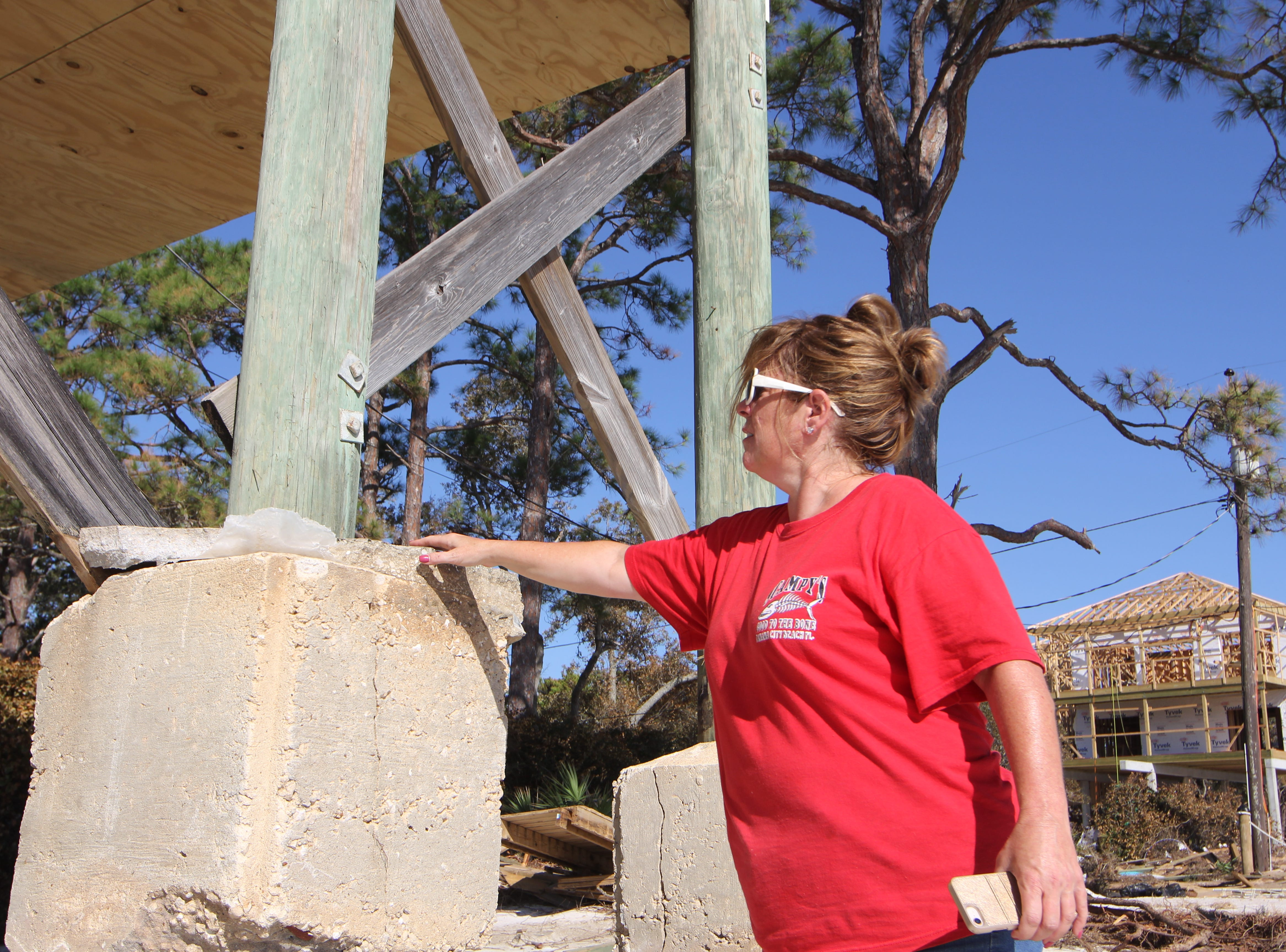 Tonia McNabb shows the where sand came up to on the pilings of her house on Alligator Point before Hurricane Michael.