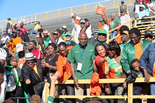 FAMU president Dr. Larry Robinson (center) and athletics director Dr. John Eason (behind) join a host of FAMU fans to celebrate the team's victory over N.C. A&T.