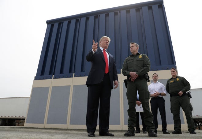 In this March 13, 2018, file photo, President Donald Trump speaks during as he reviews border wall prototypes, in San Diego, as Rodney Scott, the Border Patrol's San Diego sector chief, listens.