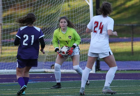 Rye's Olivia Dabinett (center) in action during a game against John Jay-Cross River last year at John Jay High School.