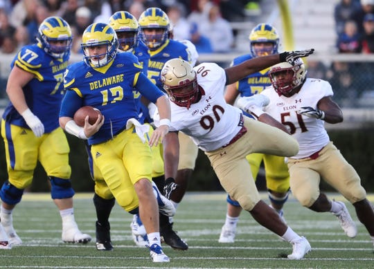 Delaware quarterback Pat Kehoe eludes Elon's Kadrien Darity in the second quarter at Delaware Stadium Saturday.