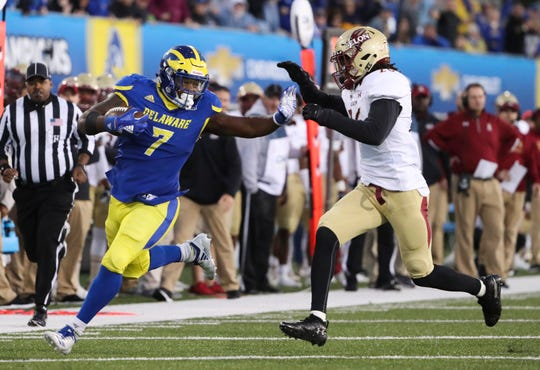 Delaware's Kani Kane fends off Elon's  Daniel Reid-Bennett at the end of a 32-yard run that helped put away the game in the fourth quarter of the Blue Hens' 28-16 win at Delaware Stadium Saturday.